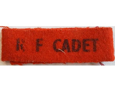 CST029. R F CADET, black printed on red wool, small size, as wor